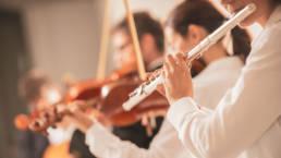 Orkesteri soittaa poikkihuilua ja viuluja